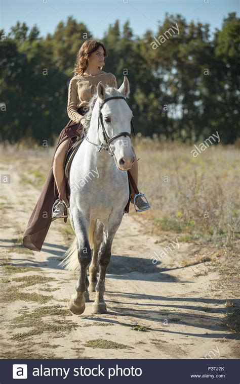 Beautiful girl riding on the white horse in a field Stock