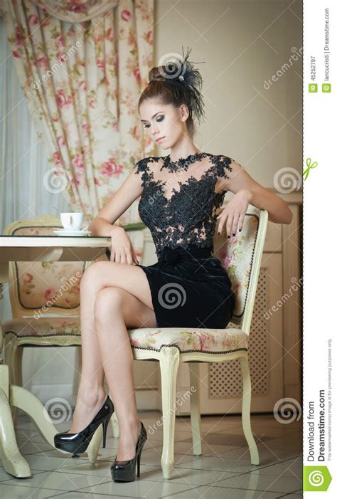 Fashionable Attractive Young Woman In Black Dress Sitting